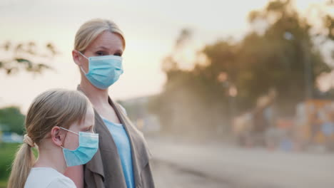 A-Woman-With-A-Child-In-Protective-Masks-Are-Standing-Near-A-Dirty-Dusty-Road-In-The-City