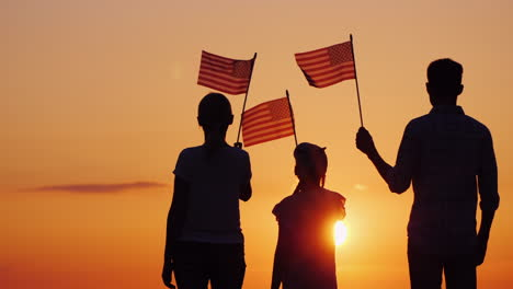 Happy-Family-With-Child-Waving-Us-Flags-At-Sunset-Rear-View