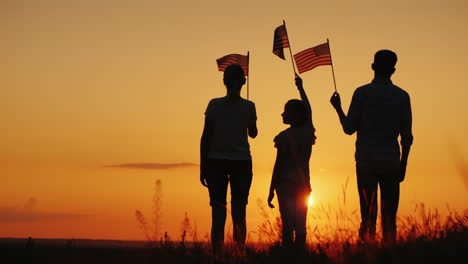 Family-With-Child-Waving-Us-Flags-At-Sunset-Rear-View