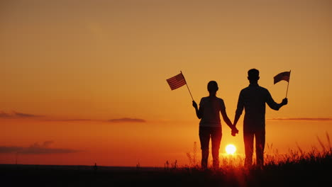 A-Young-Couple-With-The-Flags-Of-The-United-States-In-Their-Hands-Admires-The-Beautiful-Sunset-Indep