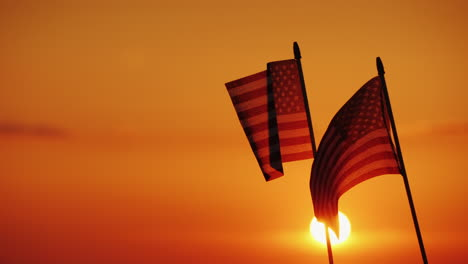 Two-American-Flags-Against-The-Setting-Sun-And-Orange-Sky