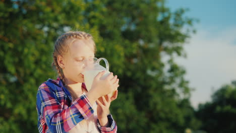 A-Girl-Drinks-Milk-From-A-Glass-Jug-In-Her-Garden-Healthy-Organic-Products-Concept