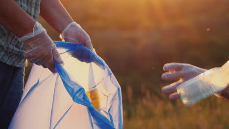 People-Put-Plastic-Trash-In-The-Bag-Clean-The-Meadow-Close-Up-Shot