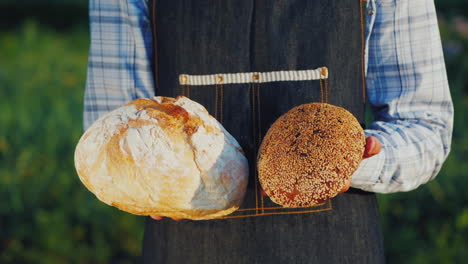 A-Baker-Holds-Two-Loaves-Of-Light-And-Dark-Bread