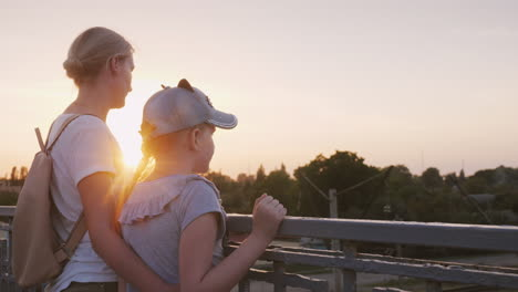 A-Woman-With-Her-Daughter-Are-Standing-At-The-Railing-Of-The-Bridge-At-Sunset-Evening-Walk-With-Mom