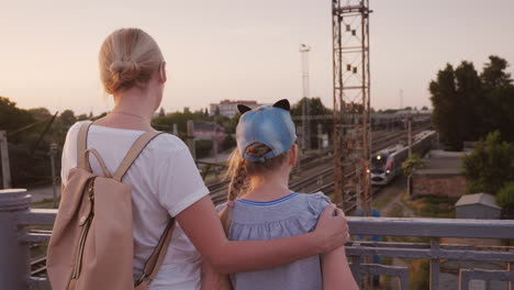 A-Woman-And-Her-Daughter-Stand-On-The-Bridges-And-Look-At-The-Train-Below