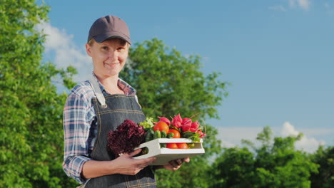 Ortrait-Of-A-Female-Farmer-With-A-Box-Of-Fresh-Vegetables-From-Her-Garden