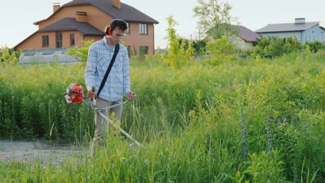 Man-Mows-Weeds-Around-The-House-With-A-Trimmer