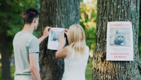 Young-Couple-Putting-Up-Missing-Pet-Banners