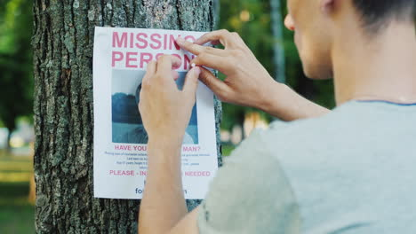 A-Young-Man-Puts-Up-Ads-For-A-Missing-Person-In-The-Park