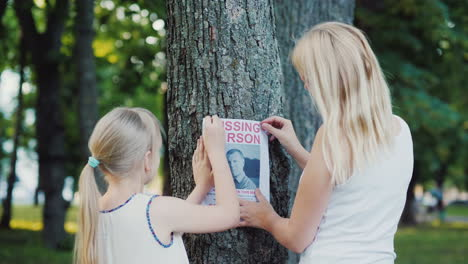 A-Woman-With-A-Child-Is-Attached-To-The-Tree-Flyer-With-Information-About-The-Missing-Man
