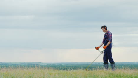 Young-Man-Mowing-Grass-With-A-Trimmer-On-A-Picturesque-Meadow