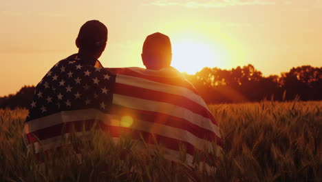 A-Man-And-His-Son-Admire-The-Sunset-Over-A-Field-Of-Wheat-Wrapped-In-The-Flag-Of-The-Usa