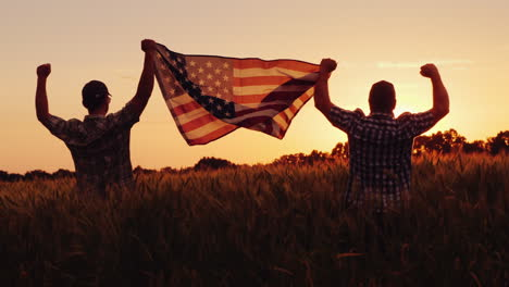 Two-Men-Happily-Raise-The-American-Flag-Over-A-Field-Of-Wheat-At-Sunset-4th-Of-July-Concept