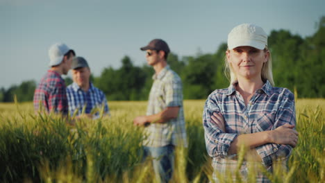 Portrait-Of-A-Young-Woman-Farmer-On-The-Background-Of-The-Field-And-Other-Farmers-Who-Communicate-Be