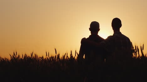 Two-Gay-Men-Stand-Hugging-At-Sunset-Looking-Forward-To-The-Horizon