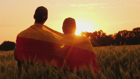 Two-Men-With-The-Flag-Of-Germany-Behind-Their-Shoulders-Are-In-A-Picturesque-Place-In-A-Field-Of-Whe