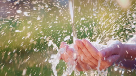Water-Flows-Into-Open-Human-Palms-Splashes-Effectively-Fly-Apart-In-The-Sun-Slow-Motion-Video