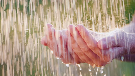 A-Man-Holds-His-Hands-In-The-Pouring-Rain-Drops-Of-Water-Fly-Apart-Cool-And-Clean-Water-Concept-Slow