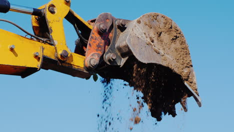From-The-Excavator-Bucket-Pouring-Soil-Against-The-Blue-Sky