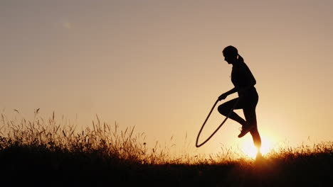 Silhouette-Of-A-Woman---Jumping-Through-The-Rope-At-Sunset