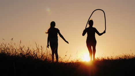 Training-In-The-Fresh-Air---A-Silhouette-Of-A-Woman-Jumping-Over-A-Rope-At-Sunset