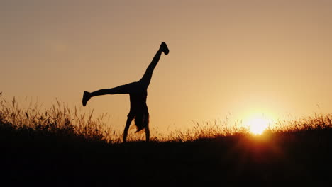 Silhouette-Of-A-Little-Girl-Making-Acrobatic-Wheel-In-A-Beautiful-Sunset-Setting
