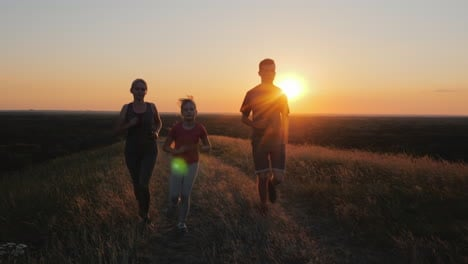A-Young-Child-With-A-Couple-Jogging-Outdoors-In-Scenic-Location-On-The-Sunset