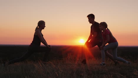 Family-With-A-Child-Doing-Exercises-Together-In-A-Picturesque-Place-At-Sunset