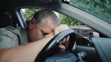 Tired-Middle-Aged-Man-Put-His-Head-On-The-Wheel-Of-A-Car