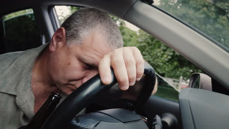 Drunk-Driver-With-A-Bottle-Of-Alcohol-In-His-Hand-Dozing-On-The-Steering-Wheel