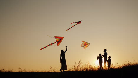 A-Young-Sam-With-Two-Children-Plays-Kites-At-Sunset-In-A-Picturesque-Place-Family-Activity-Outdoors