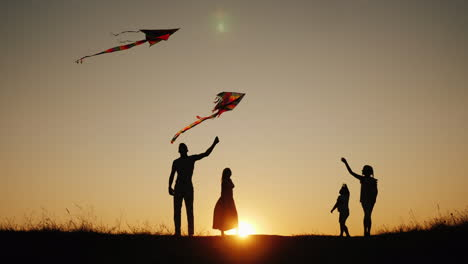 Active-Family-With-Children-Launches-Kites-In-A-Picturesque-Place-At-Sunset