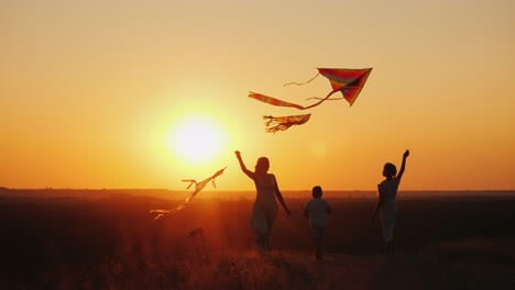 A-Woman-With-Two-Children---A-Girl-And-A-Boy-Playing-Kites-Active-Lifestyle