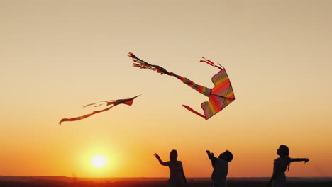 Two-Children-With-Mom-Play-Kites-At-Sunset-Good-Time-Together