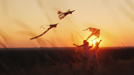 Active-Healthy-Middle-Aged-Woman-Plays-With-Two-Children-Kites-At-Sunset-Summer-Vacation-Concept