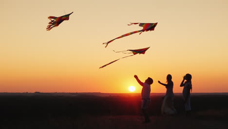 Children-With-Mom-Play-A-Kite-At-Sunset-On-A-Summer-Evening-Active-Parents-And-Children