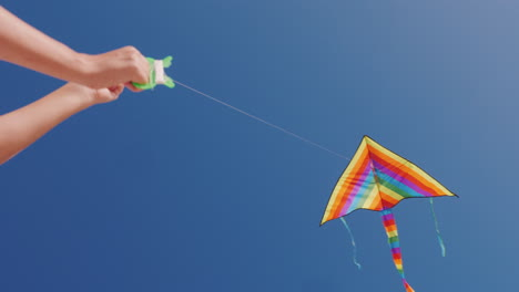 Man-Controls-Kite-That-Hovers-In-Blue-Cloudless-Sky-Low-Angle-Shot