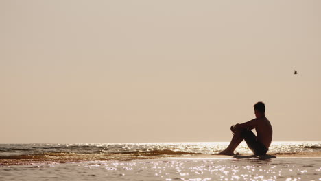 Lonely-Silhouette-Of-A-Young-Man-Sitting-On-The-Sand-By-The-Sea