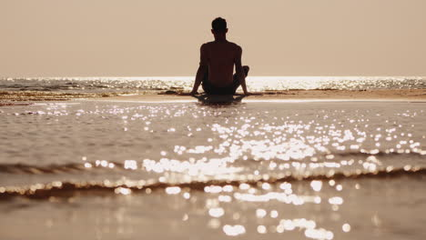 Silhouette-Of-A-Young-Man-Sitting-On-A-Small-Sand-Island