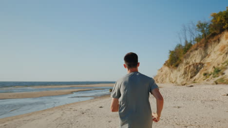 Young-Man-Jogging-On-The-Beach-In-A-Picturesque-Place