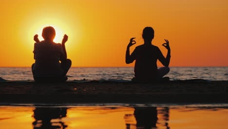 Grandmother-And-Granddaughter-Meditate-On-The-Beach-Active-And-Healthy-Seniors-Concept