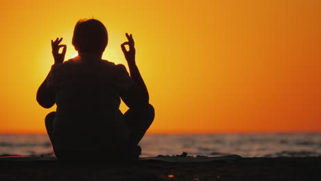 Senior-Woman-Meditates-In-A-Picturesque-Place-At-Sunset
