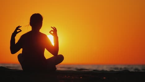 Young-Woman-Meditates-In-A-Picturesque-Place-At-Sunset