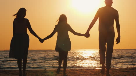 Family-With-A-Child-Goes-To-The-Sea-At-Sunset