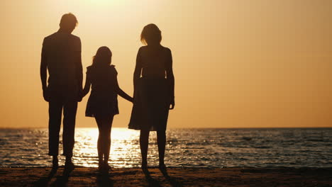 A-Young-Family-With-A-Child-Cuddles-And-Looks-Forward-To-The-Sunset-Over-The-Sea-Good-Time-Together-