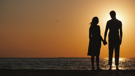 Silhouettes-Of-A-Young-Couple-In-Love-Standing-Near-The-Sea-At-Sunset