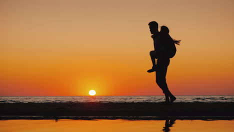 A-Young-Man-Plays-With-A-Child-Carries-Him-On-His-Shoulders-On-The-Beach