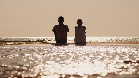A-Young-Couple-Sits-On-A-Sandy-Island-And-Looks-Forward-To-The-Horizon