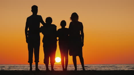 Happy-Multi-Generational-Family-Enjoying-Sunset-Over-The-Sea